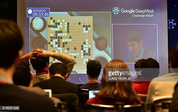 Journalists watch a big screen showing live footage of the third game of the Google DeepMind Challenge Match between Lee SeDol one of the greatest...