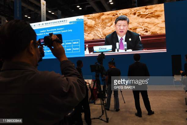 Journalists watch a live image of Chinese President Xi Jinping speaking at the leaders summit of the Belt and Road Forum in the media center of the...