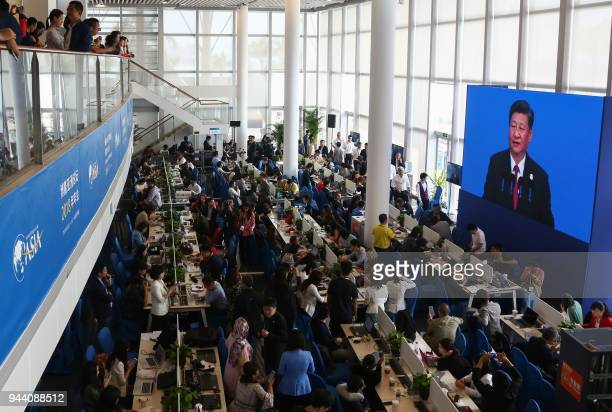 Journalists watch a screen showing a live image of China's President Xi Jinping as he delivers a speech during the opening of the Boao Forum for Asia...