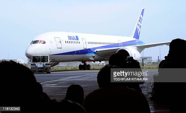 Journalists watch an All Nippon Airways Boeing 787 Dreamliner moving into a hangar during a media viewing at Haneda airport in Tokyo on July 4, 2011....