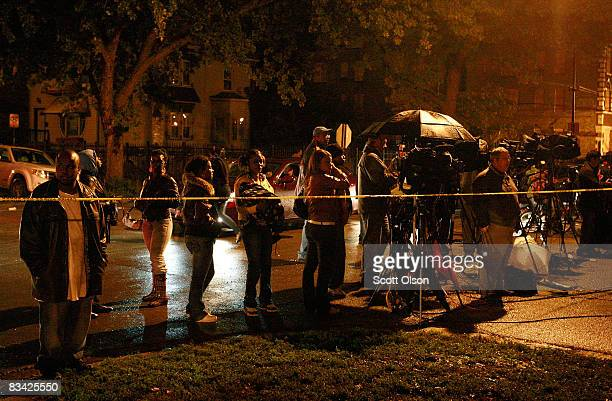 Journalists watch behind police tape as police work and investigate in the Englewood neighborhood where 57yearold Darnell Hudson Donerson the mother...