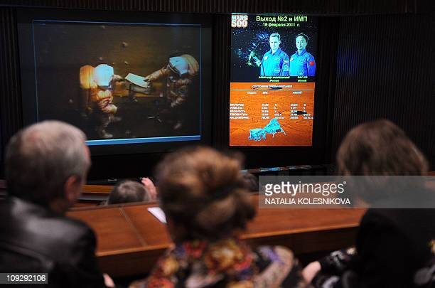 Journalists watch on February 18 2011 a mock walk on Mars of volunteers of the Mars500 experiment Van Yue of China and Alexander Smoleyevsky of...