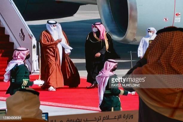 Journalists watch, Saudi Crown Prince Mohammed bin Salman welcomes the Emir of Qatar Tamim bin Hamad Al-Thani , on a screen in the media centre ahead...