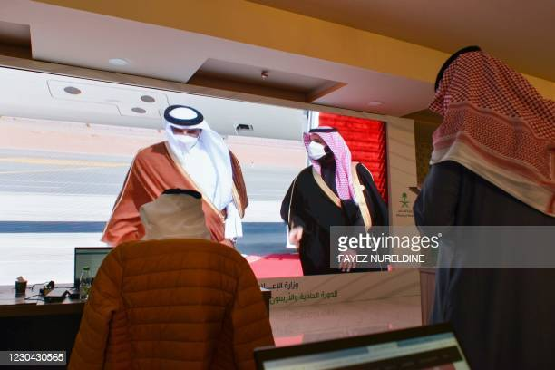 Journalists watch, Saudi Crown Prince Mohammed bin Salman welcomes the Emir of Qatar Tamim bin Hamad Al-Thani , on a screen in the media centre ahead...