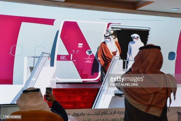 Journalists watch the arrival of the Emir of Qatar Tamim bin Hamad Al-Thani ahead of the 41st Gulf Cooperation Council summit in the city of al-Ula...