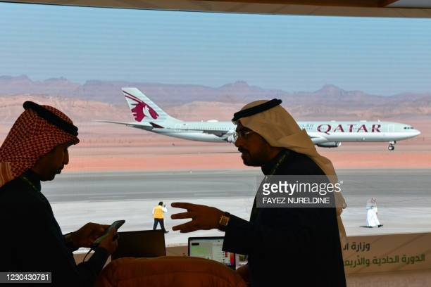 Journalists watch the arrival of the Qatar envoy ahead of the 41st Gulf Cooperation Council summit in the city of al-Ula in northwestern Saudi Arabia...