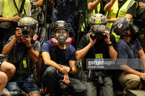 TOPSHOT Journalists wear protective gear and high visibility vests during a press conference to highlight allegations that police have mistreated and...