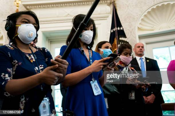 Journalists with face masks ask President Donald Trump questions during a signing ceremony for H.R. 266, the Paycheck Protection Program and Health...