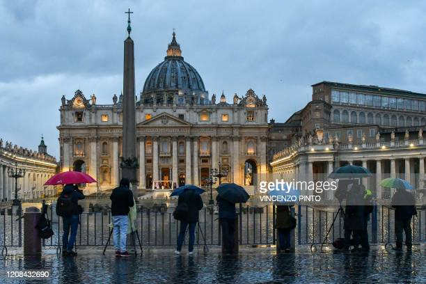 Journalists work as Pope Francis presides over a moment of prayer on the sagrato of St Peters Basilica, the platform at the top of the steps...