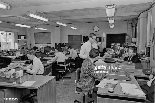Journalists work at desks in the news room office of Independent Television News in London in July 1967.