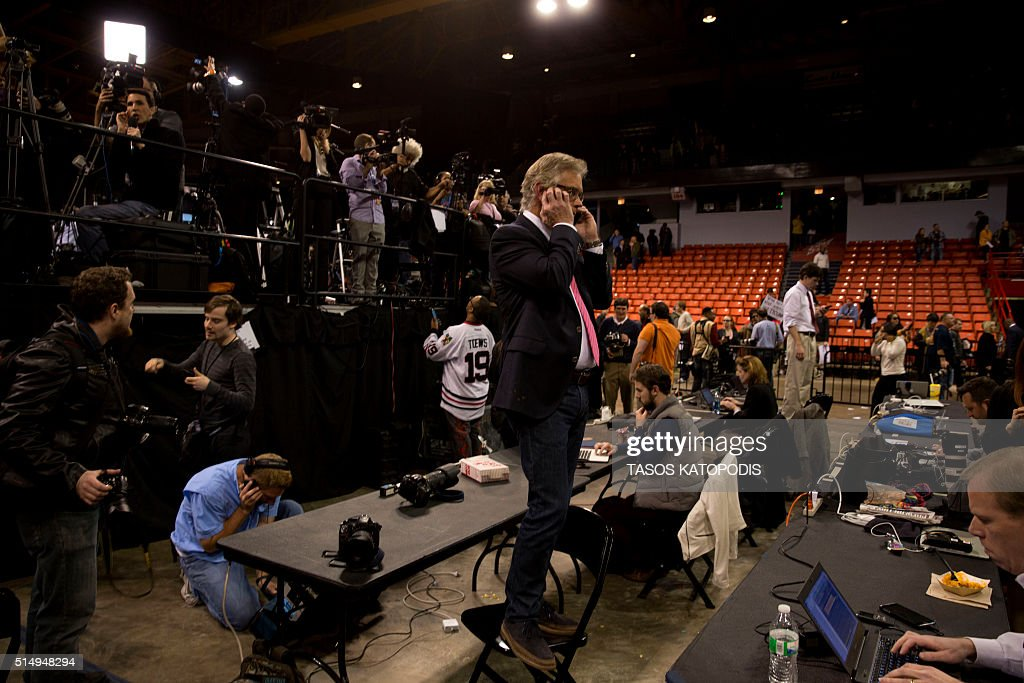Journalists work during a Trump rally at the UIC Pavilion in Chicago on March 11, 2016. Republican White House hopeful Donald Trump cancelled his appearance at a Chicago rally Friday amid extraordinary scenes of chaos, with hundreds of protesters clashing with the frontrunner's supporters and police struggling to maintain order. / AFP / Tasos KATOPODIS