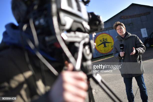 Journalists work in front of La Vache rit a farm in the 'Zad' of NotreDamedesLandes after French prime minister announced the French government's...