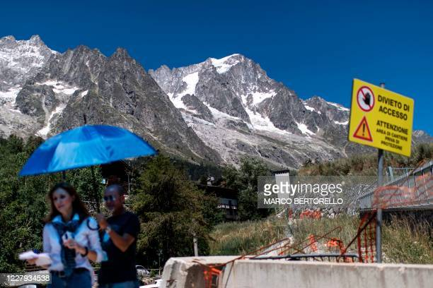 "Journalists work next to a sign reading ""Access denied"" in front of the Planpincieux glacier in the village of La Palud, in Courmayeur, Val Ferret,..."