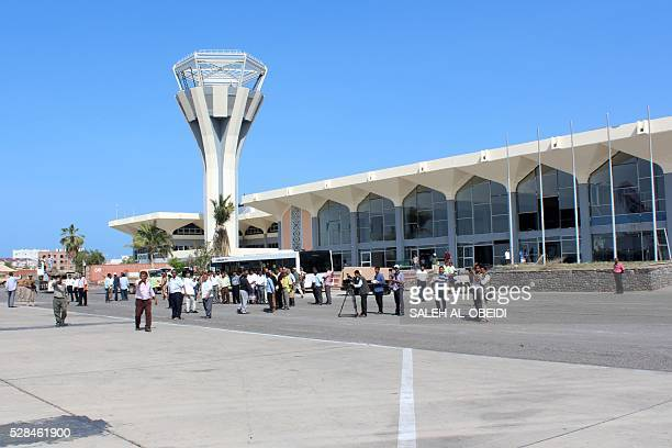 Journalists work on May 5 2016 at the International Airport of the southern port city of Aden as the first passenger plane landed after the airport...