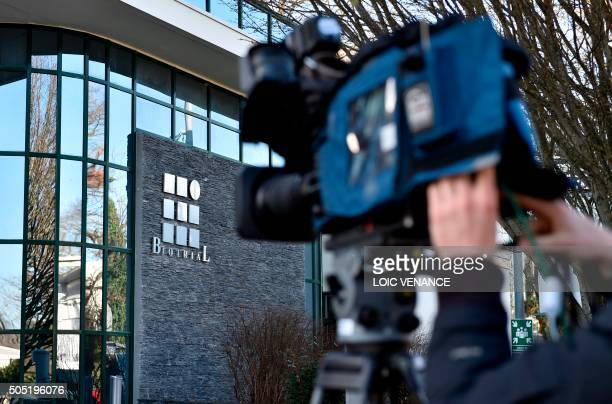 Journalists work outside the Biotrial laboratory headquarters building with its logo in Rennes western France on January 16 after a clinical trial of...
