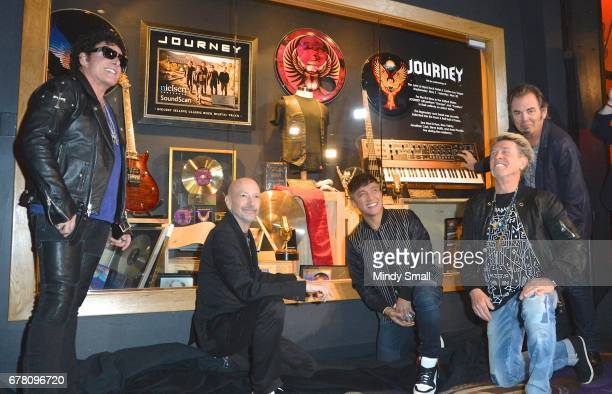 Journey band members Neal Schon Steve Smith Arnel Pineda Ross Valory and Jonathan Cain pose during the Journey Memorabilia Case dedication at the...