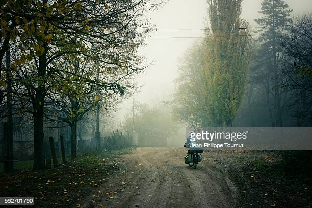 A journey by bicycle around the world, young adventurous woman cycling in the fog on a dirt road of Georgia, Eurasia