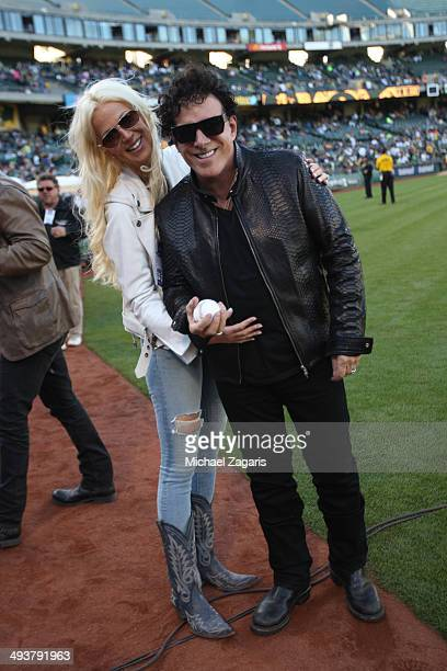 Journey guitar player Neal Schon stands on the field with his with Michaele Salahi prior to the game between the Washington Nationals the Oakland...