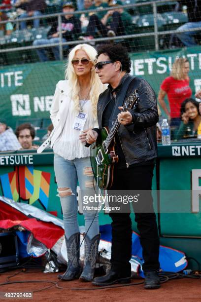 Journey guitar player Neal Schon stands on the field with his with Michaele Salahi before performing the anthem prior to the game between the...