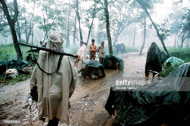 Journeying through the forest with a guerrilla unit starving refugees head towards the Thai border in the pouring monsoon rains