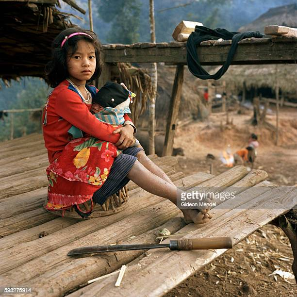 Joushou cradles her younger brother in the Ban Nam Lai Akha village The Akha are a hill tribe of subsistence farmers known for their artistry This is...