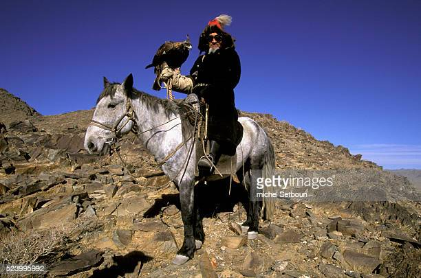 Jousting in the Kazakh province The competitors gather on the mountain tops that rise over the plains Below a rider drags the body of a dead fox skin...