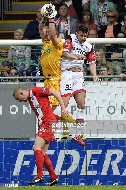 Jovan Kostovski of OH Leuven battles for the ball with goalkeeper Alexandre Oukidja of Mouscron and Benjamin Delacourt of Mouscron during match day 1...