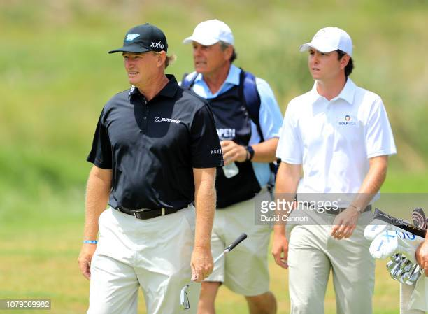 Jovan Rebula of South Africa walks behind his uncle Ernie Els of South Africa as they walk to the green on the seventh hole during the third round of...