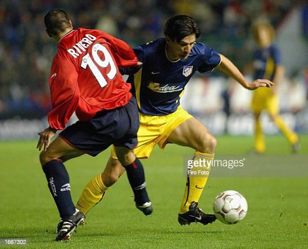 Jovan Stankovic of Atletico is challenged by Gerardo Rivero of Osasuna during the Osasuna v Atletico Madrid La Liga match played at the El Sadar...