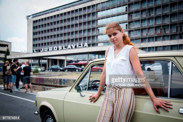 """Jovana Stojiljkovic, manager of the Yugotour agency, poses for a picture on May 25, 2018 by a Yugoslav era popular car """"Zastava 101"""", in front of the..."""