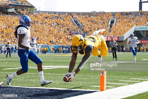 Jovani Haskins of the West Virginia Mountaineers dives into the end zone for a 14yard touchdown after catching a pass against the Kansas Jayhawks in...