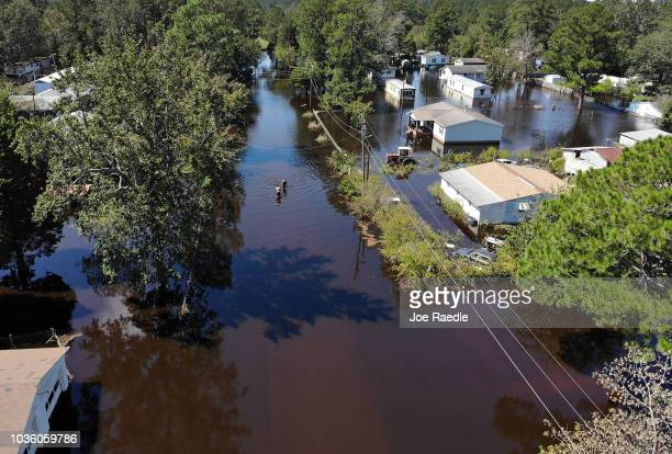 Jovani Quintano and Carlos Gomez walk through a flooded neighborhoom after heavy rains brought on by Hurricane Florence on September 19 2018 in...