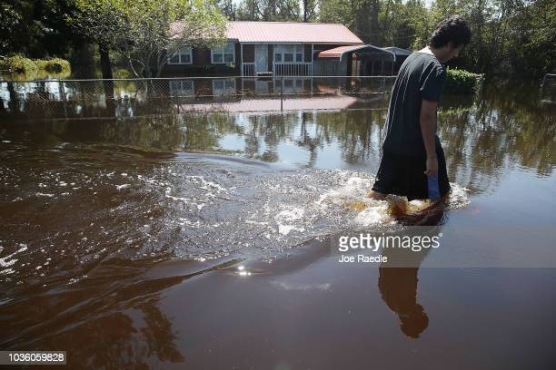 Jovani Quintano walks through a flooded neighborhood after heavy rains brought on by Hurricane Florence on September 19 2018 in Lumberton North...