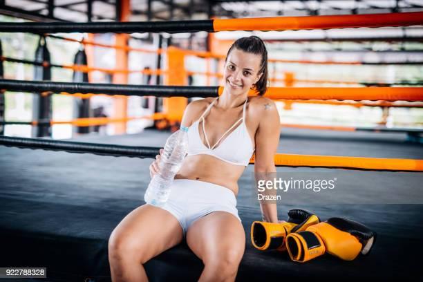 Jovem mulher brasileira exercitando boxe para senhoras e descansando após o treinamento