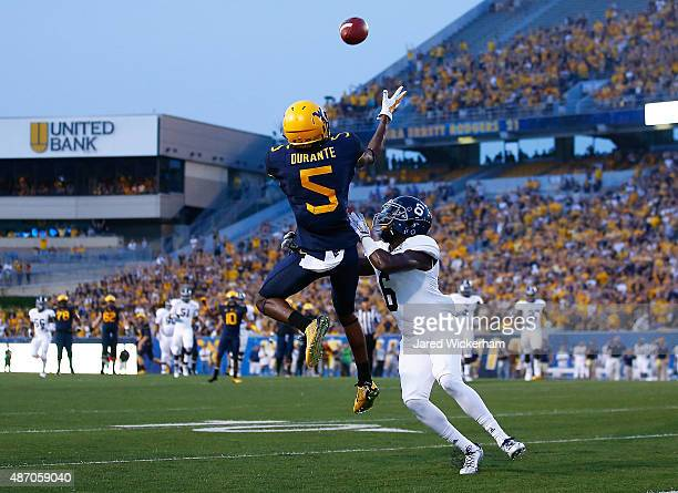 Jovon Durante of the West Virginia Mountaineers catches a touchdown pass in front of Dravon AskewHenry of the Georgia Southern Eagles in the first...
