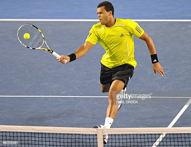 JoWilfried Tsonga of France hits a volley return against Novak Djokovic of Serbia in their men's singles quarterfinal match on day 10 of the...