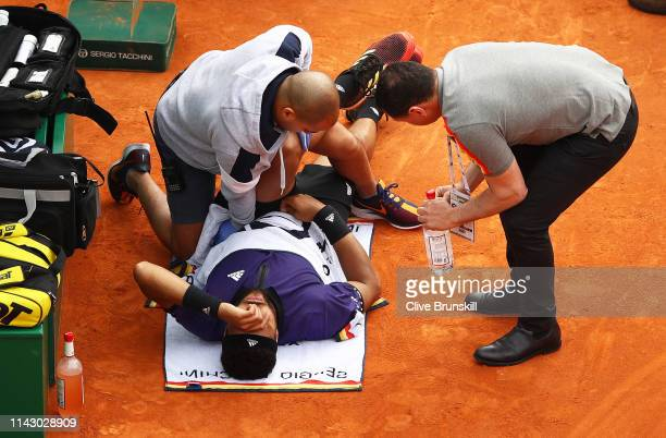 JoWilfried Tsonga of France receives treatment on court before retiring injured against Taylor Fritz of the United States in their first round match...