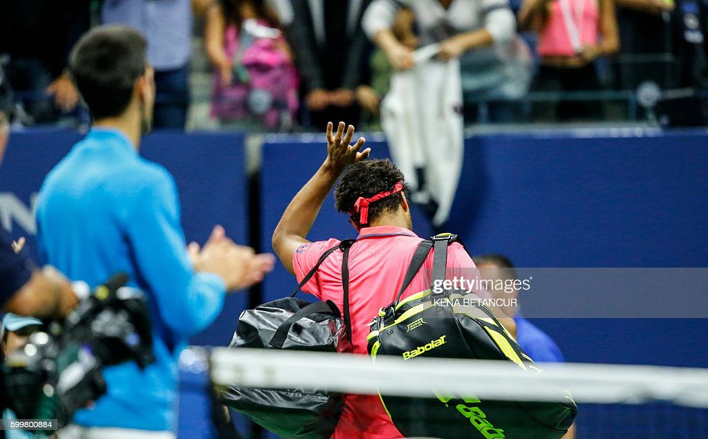 TOPSHOT - Jo-Wilfried Tsonga of France waves after retiring due to injury after playing against Novak Djokovic of Serbia (L) in their 2016 US Open Men's Singles match at the USTA Billie Jean King National Tennis Center in New York on September 6, 2016. Defending champion Novak Djokovic reached his 10th successive US Open semi-final when Jo-Wilfried Tsonga retired from their quarter-final with a left knee injury while trailing 6-3, 6-2. / AFP / KENA