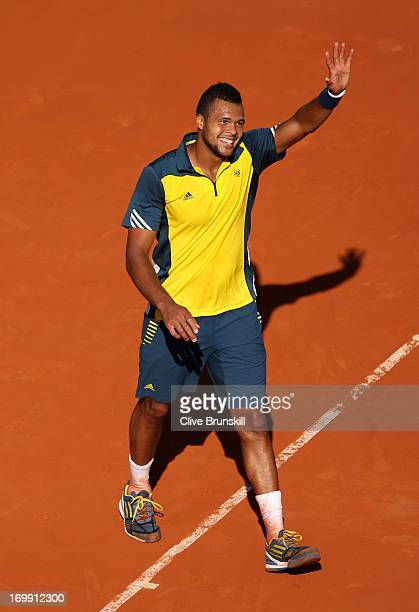 Jo-Wilfried Tsonga of France waves to crowd after victory in his Men's Singles quarter final match against Roger Federer of Switzerland during day...