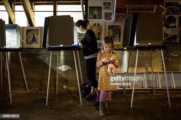 Joy Alferness votes in the California primaries while her daughter Eden Alferness age 5 plays on a phone on June 7 2016 in the Potrero hill...