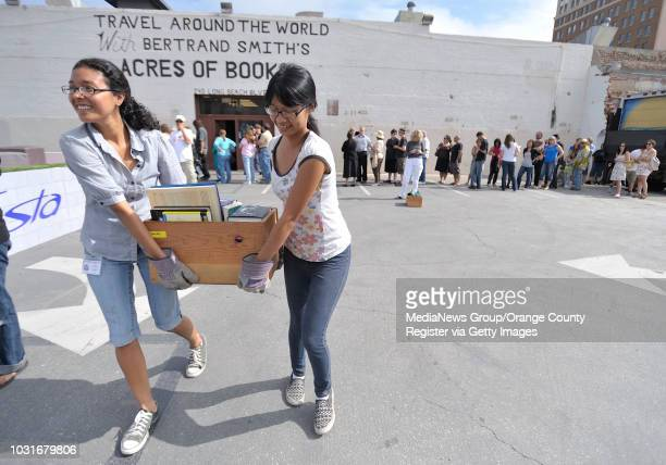 USA Joy Contreras left and Linda Nguyen help a customer carry their books during Acres of Books' last hurrah in Long Beach CA on July 10 2010 The...