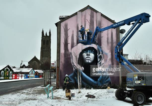 Joy Gilleard and Haley Garner of the street art duo Nomad Clan continue work on a large mural on the Newtownards road on March 1 2018 in Belfast...