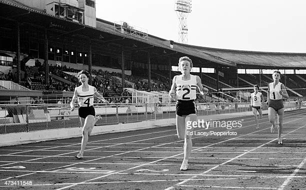 Joy Grieveson of Great Britain crosses the finish line to win the 440 yards race setting the European Record time of 532 seconds followed by Ann...