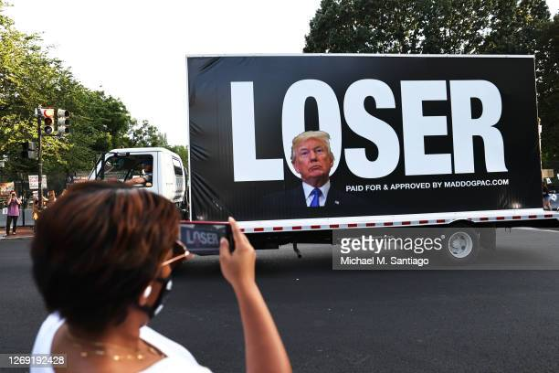 "Joy Jackson photographs a passing truck bearing an image of U.S. President Donald Trump in front of block letters reading ""LOSER"" at Black Lives..."