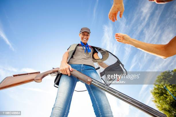 joy of a female skeet shooting champion after winning - stock photo - clay pigeon shooting stock pictures, royalty-free photos & images