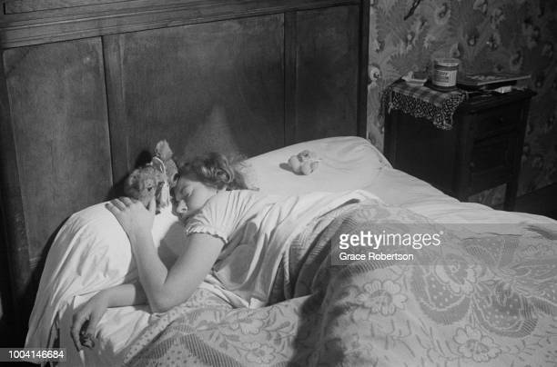 Joy the head girl of a Bluebell Girls dance troupe sleeps accompanied by a cuddly koala toy in her room at the Hotel Riboute in Paris November 1951...