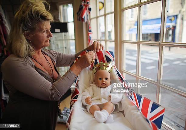 Joy Wright dresses a baby doll in the window of the Tenovus charity shop to celebrate the Royal birth on July 23 2013 in Tetbury England Catherine...