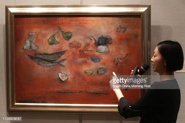 """Joyce Chan, assistant vice president Specialist, Asian 20th Century & Contemporary Art Christie's Hong Kong shows a print """"Nature morte aux poisson""""..."""