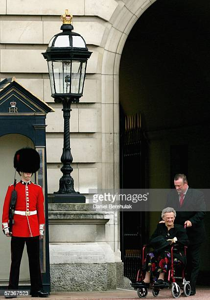Joyce Kozial smiles as she is ushered past one of the Queen's Foot Guards as she departs after her lunch with the Queen at Buckingham Palace on April...