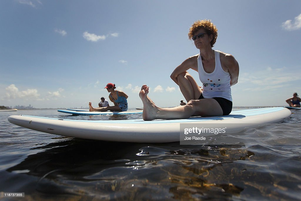 Joyce Landry and others enjoy a paddleboard yoga session at Adventure Sports Miami on July 10, 2011 in Miami, Florida. The paddle board is said to give the body's core more of a workout then in a gym since the platform is unstable and one must use the muscles to remain balanced on the board.